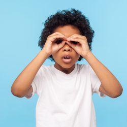Curious child exploring world. Portrait of inquisitive little curly boy looking through fingers shaped like binoculars and expressing amazement. indoor studio shot isolated on blue background