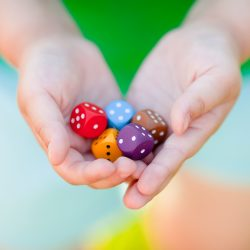 Mixed color dices in child's hands. Board games for kids.
