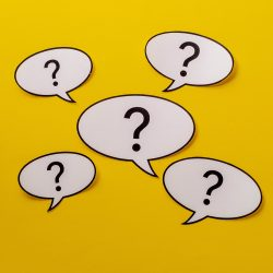 Five speech bubbles with question marks centered over a bright yellow background
