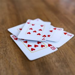 Five hearts cards on table