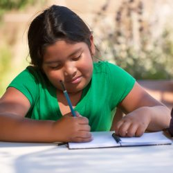 Elementary student using imagination to sketch ideas on notebook in an outdoor setting while the sun is setting.
